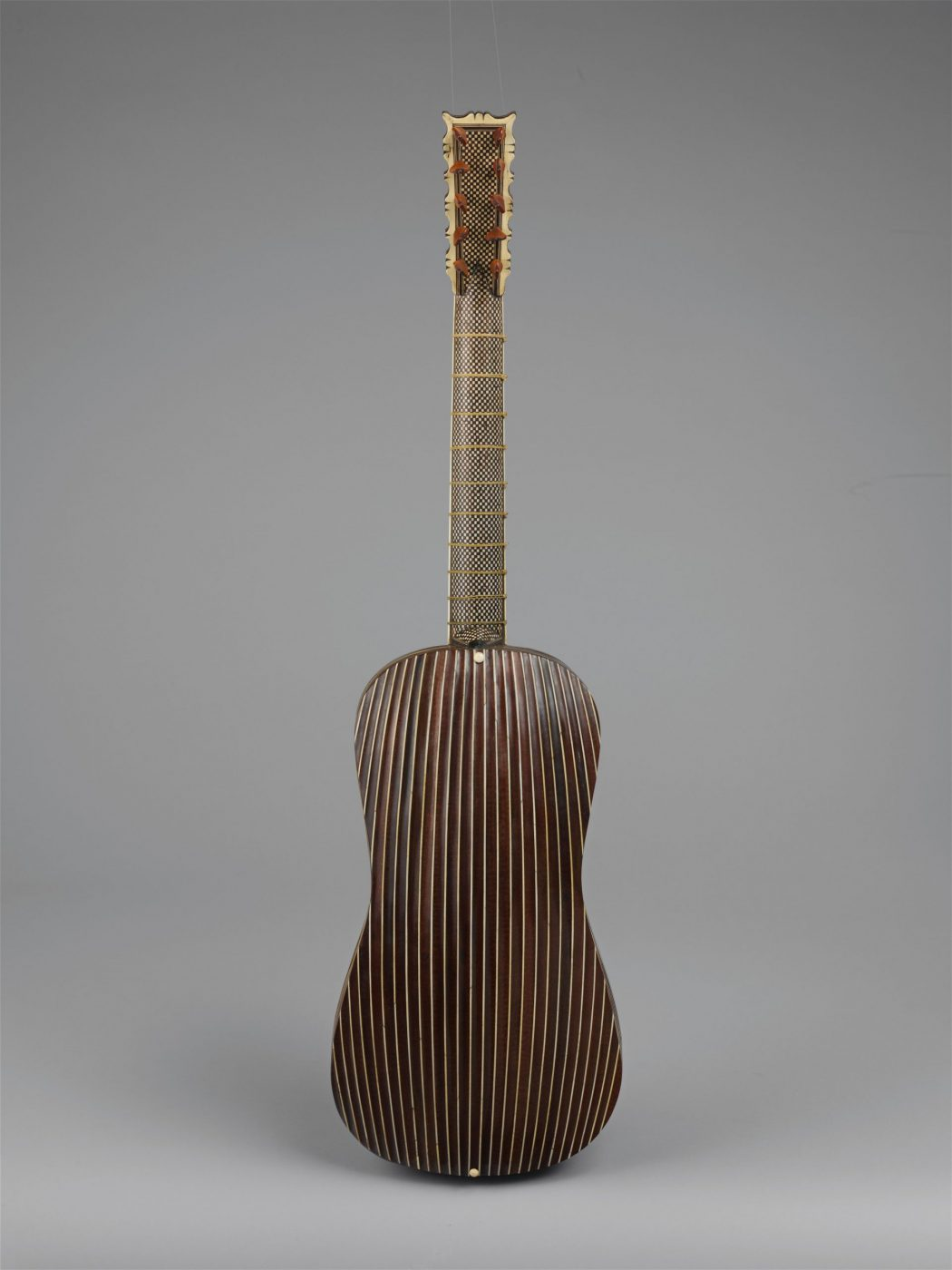 Back of Baroque guitar with many ribs and geometric pattern on neck