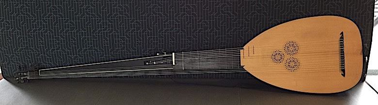long-necked theorbo lying across almost the entire length of a grey bench