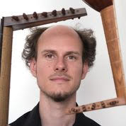Bor Zuljan's head framed by two lute pegboxes